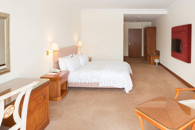 White bed and tables with chairs in light hotel room. — Stock Photo