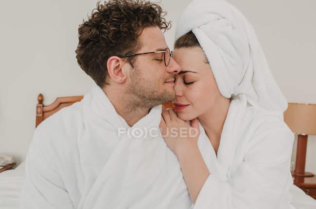 Sensual man and woman in bathrobes cuddling on bed. — стоковое фото