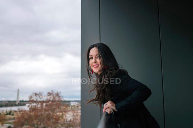 Femme joyeuse s'appuyant sur la main courante et souriant à la caméra — Photo de stock