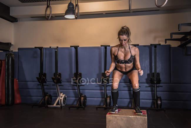 Convient à la formation des femmes blondes et à l'entraînement avec une boîte dans un gymnase — Photo de stock