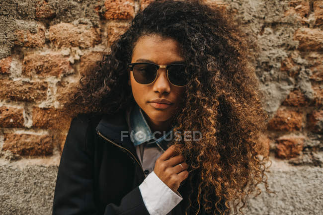 Stylish curly woman posing at brick wall and touching collar — Stock Photo