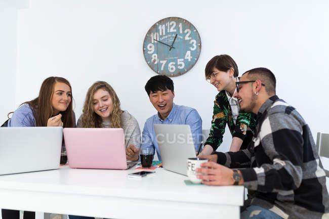 Grupo de alegres multirraciais colegas sentados juntos com gadgets na mesa — Fotografia de Stock