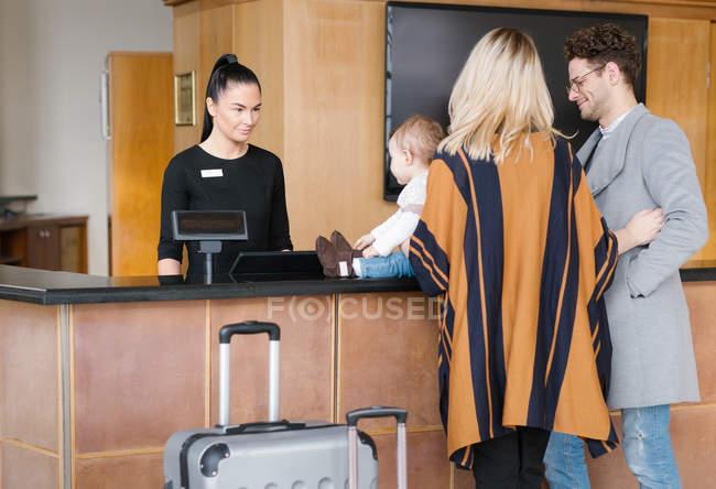 Vista trasera de la joven familia en la recepción del hotel - foto de stock