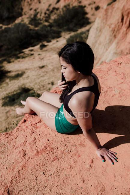 Menina morena jovem sentado na colina e olhando para baixo — Fotografia de Stock