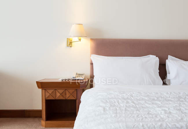 Crop bed and lit lap at hotel room — Stock Photo