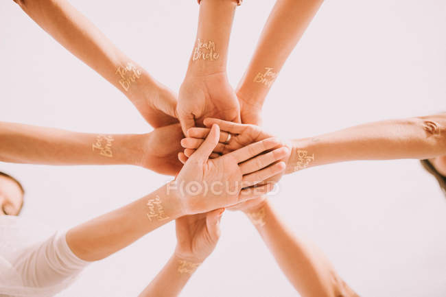 From below hands in circle of cheering people with Team Bride words on wrists. — Stock Photo