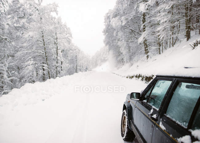 Cropped image of car parked on snowy road in winter. — Stock Photo