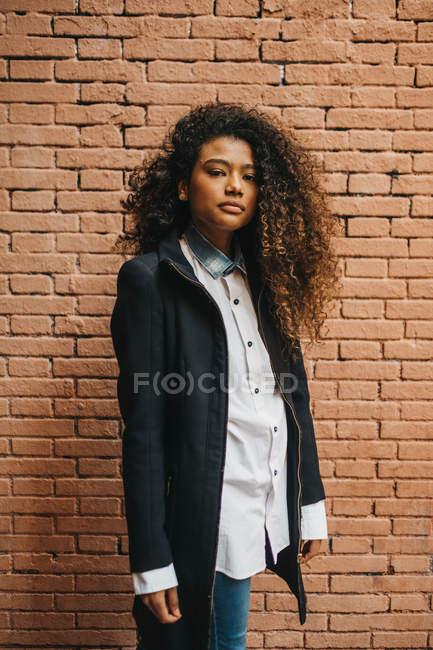 Elegante mujer joven rizado de pie en la pared de ladrillo - foto de stock