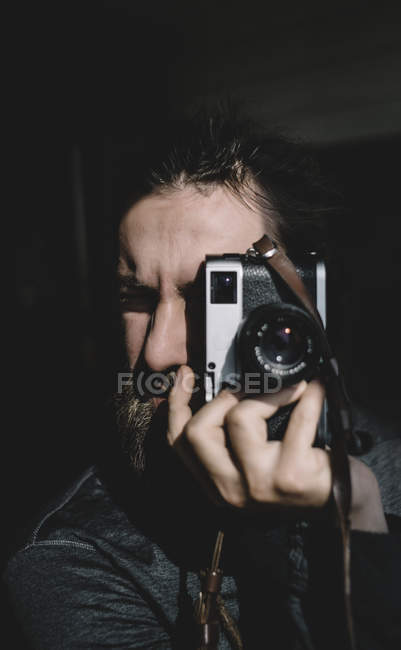 Photographer over black and focusing with vintage camera — Stock Photo