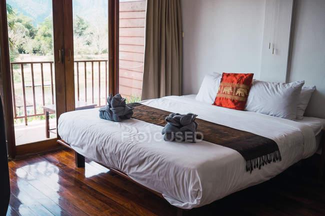 Интерьер гостиничного номера с готовым полотенца на кровати — стоковое фото
