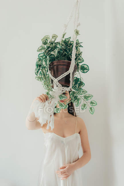 Young woman holding cache pot made of hanging ropes on white background. — Fotografia de Stock