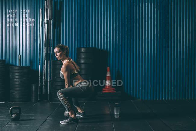 Vue latérale d'ajustement femme accroupie kettlebell en gym — Photo de stock