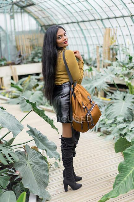 Молодой стильный индийский \woman с рюкзаком, стоя в теплицу и глядя через плечо на камеру — стоковое фото