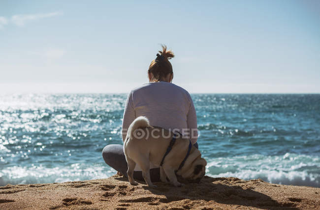 Rear view of woman sitting on sea shore in spring day with Pug dog — Stock Photo