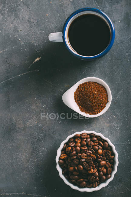 Coffee cup with coffee beans and ground coffee in line — Stock Photo