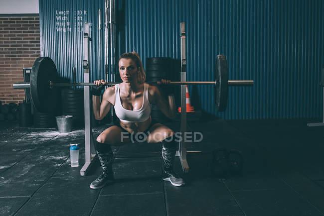 Fit blonde Frau hocken mit bar Gewichte im Fitnessstudio — Stockfoto