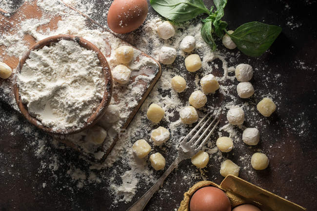 Directly above view of table with raw gnocchi and ingredients on table — Stock Photo