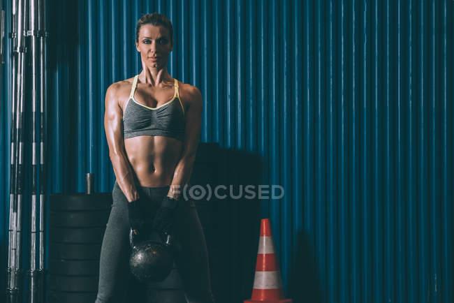 Подтянутая женщина позирует с гирей в спортзале и смотрит в камеру — стоковое фото