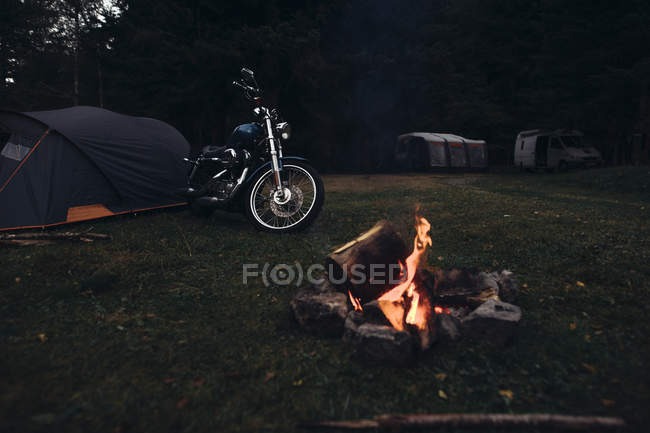 Retro motorcycle parked at campfire in nature in evening dusk — Stock Photo