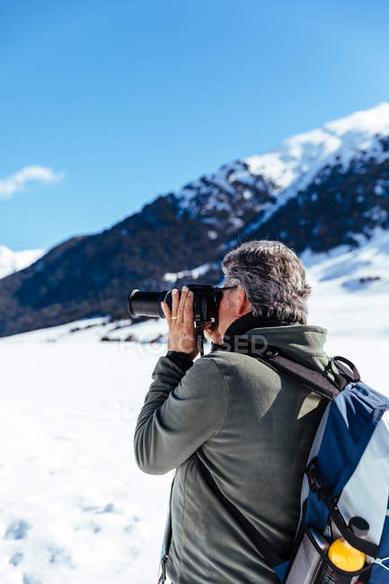 Side view of photographer taking pictures of mountains in snow — Stock Photo