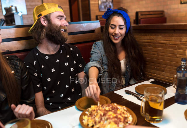 Cheerful young friends eating fast food in cafe together. — Stock Photo