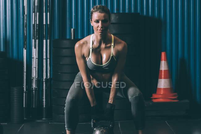 Vue de face de fit femme accroupie avec kettlebell en gym — Photo de stock