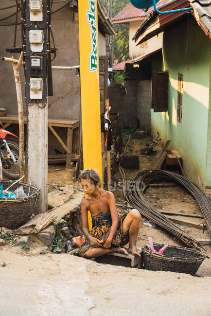 LAOS- FEBRUARY 20, 2018: Poor homeless Asian woman sitting and leaning on post at roadside. — Stock Photo