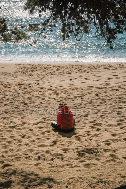 Задній вид зрілої жінки читання книг на морські пляжі — стокове фото