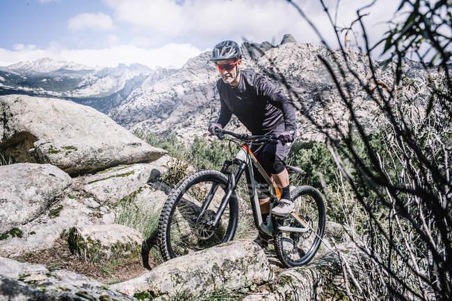 Motociclista madura, subindo a colina rochosa com bicicleta de montanha. — Fotografia de Stock