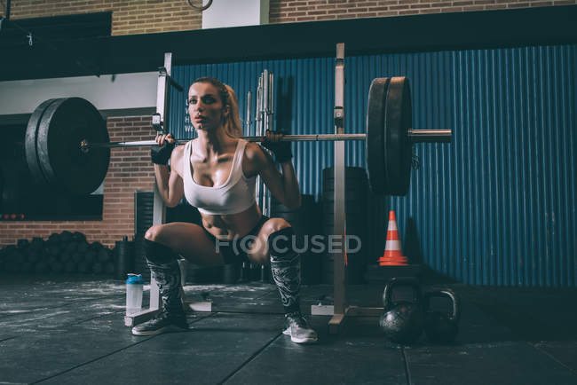 Fit blonde woman training squatting and lifting bar weights in gym — Stock Photo