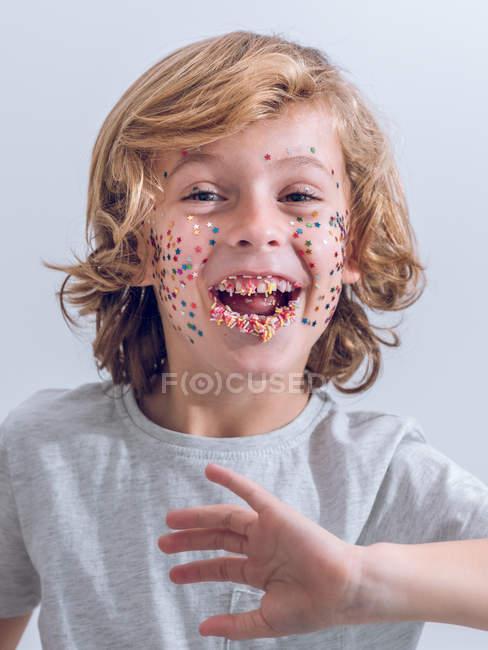 Веселый мальчик с конфетти на лице, смотрящий в камеру — стоковое фото
