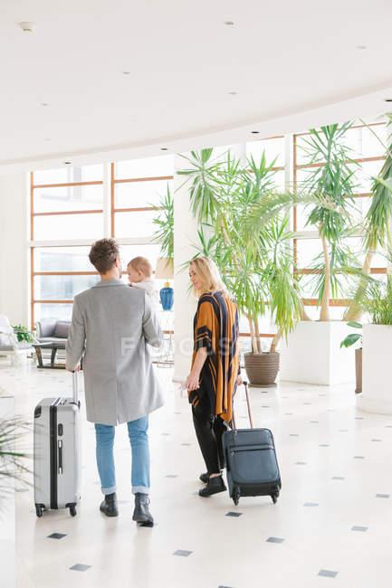Vista trasera de la joven familia con maletas en el pasillo del hotel - foto de stock