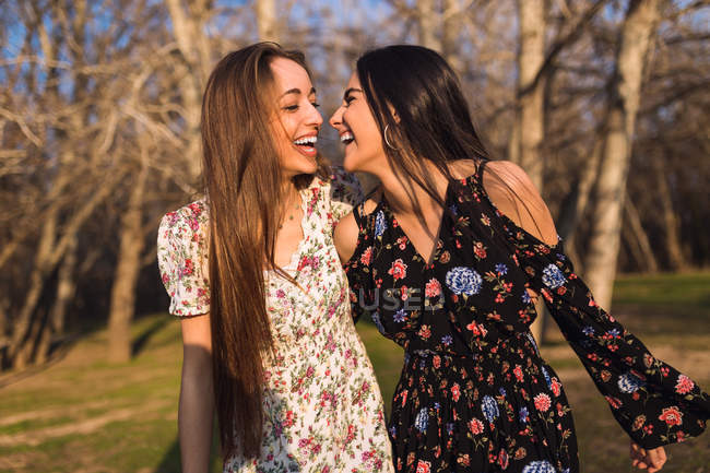 Two laughing girls embracing in sunny woods together. — Stock Photo