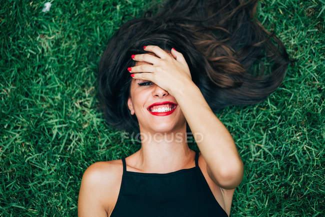 Fröhliche brünette Frau liegt im Gras und versteckt Gesicht — Stockfoto