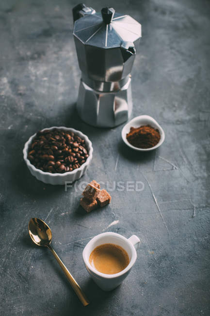 Still life of coffee maker, espresso cup and ingredients on table — Stock Photo