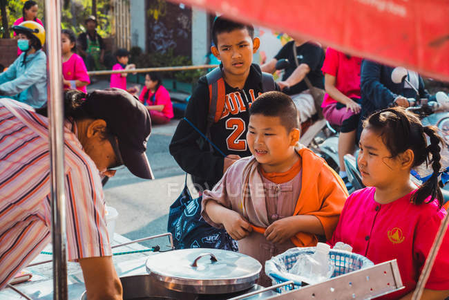 CHIANG RAI, THAILAND- FEBRUARY 9, 2018: Young teenagers standing on town street and buying food. — Stock Photo