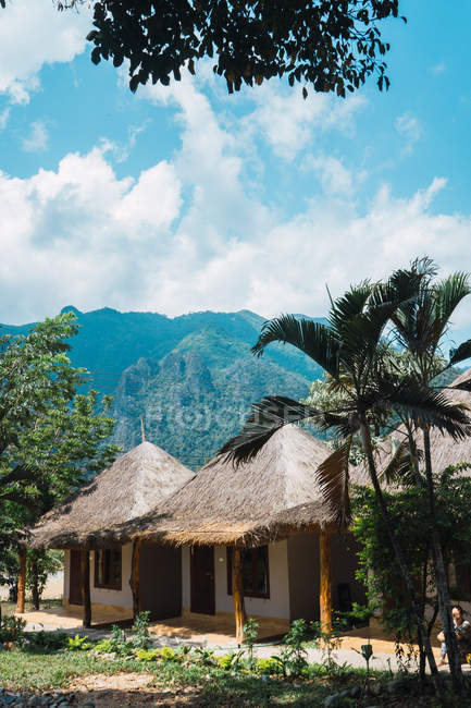 Cute small bungalows with straw roof over tropical jangle on background — Stock Photo