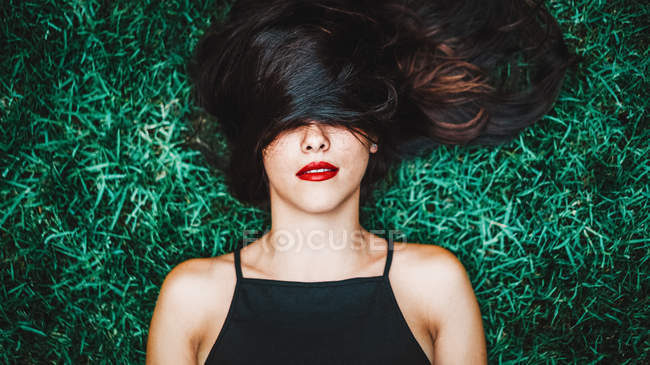 Cheerful brunette woman lying in grass with lock of hair over eyes — Stock Photo