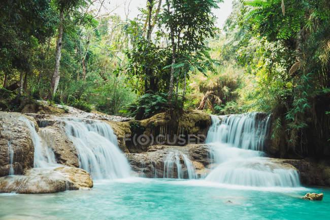 Живописные небольшие водопады, течет на голубое озеро в зеленом лесу — стоковое фото
