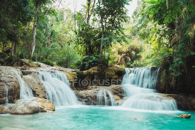 Picturesque small waterfalls flowing to blue lake in green forest. — Stock Photo