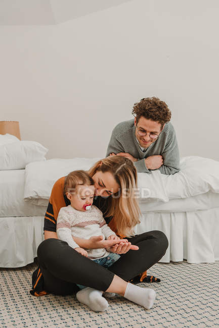 Cheerful couple with child chilling on bed — Stock Photo