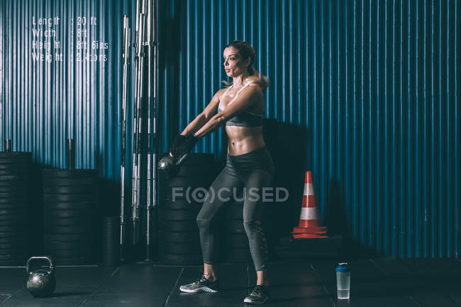 Fit blonde woman training with kettlebell in gym — Stock Photo