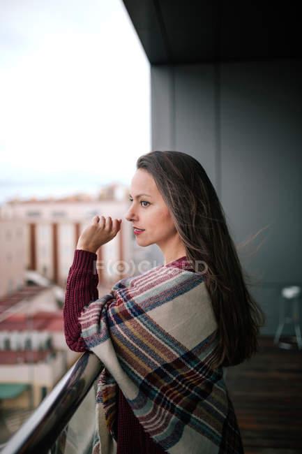 Sourire de femme brune enveloppée dans plaid posant à main courante — Photo de stock