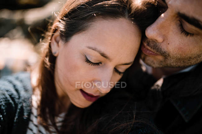 Adult couple embracing with eyes closed in sunny day. — Stock Photo