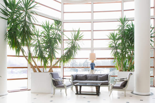 Chairs and table by potted plants at hotel lobby — Stock Photo