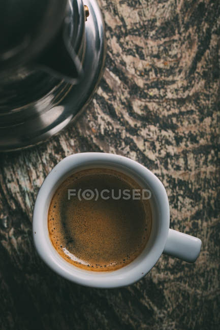 Directly above view of cup of coffee on rustic wooden table — Stock Photo