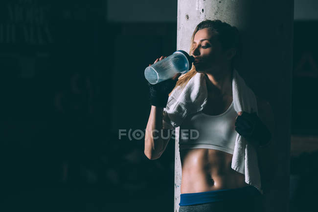 Fit blonde tired woman drinking after training out in Gym — стоковое фото
