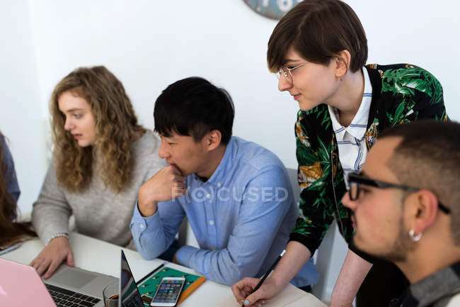 Group of coworkers sitting with gadgets at table and brainstorming together. — Stock Photo