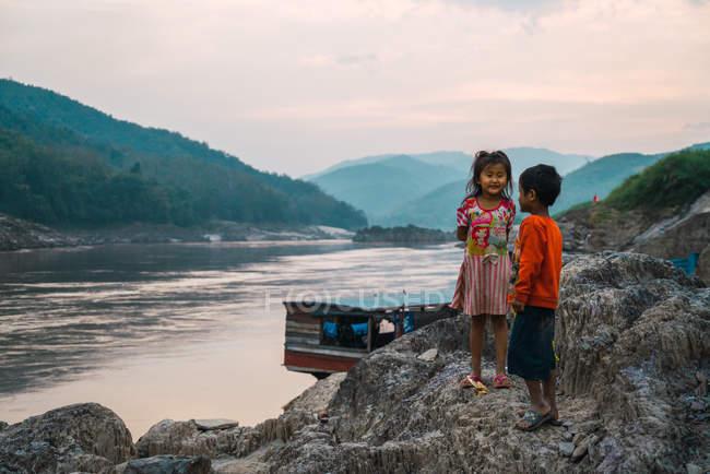 Laos- 18. Februar 2018: Niedliche Jungen und Mädchen stehen auf einem Felsen am Fluss. — Stockfoto