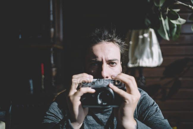 Photographer posing with vintage camera and looking at camera — Stock Photo